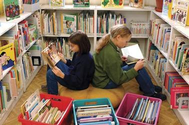 2 girls reading in the library